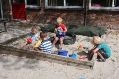 Kinderen spelen in de zandbak - Kids First COP groep